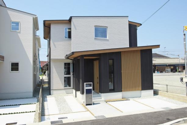 木材の格子を取り入れた和風スタイルのお家。木材の自然な茶色に黒のサイディングを合わせ、シックで大人の印象に。