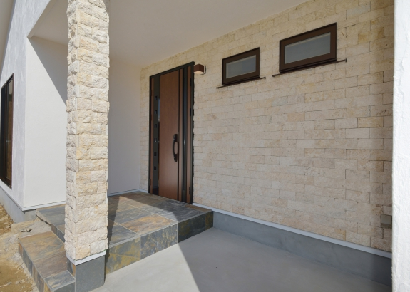 珊瑚や貝の化石が入った石灰岩のコーラルストーンがアクセントの玄関