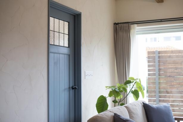 ブルーグレーのリビングドアはアンティークな空間のアクセントを演出。