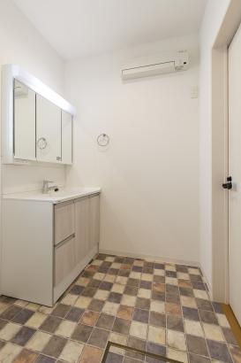 タイル調のフロアが可愛い洗面所には、三面鏡やコンセントなど設備も充実。