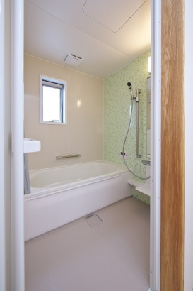 緑のアクセントパネルが爽やかな浴室。