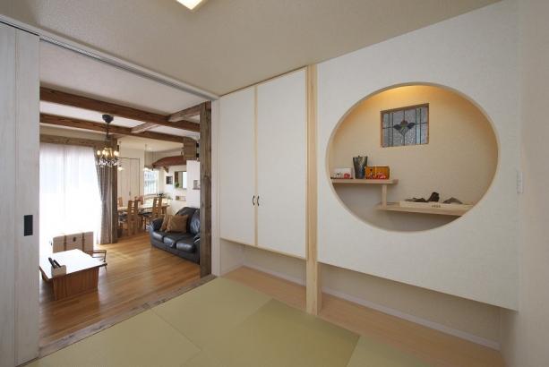 大きな円形の切り込みのある和室は料亭の様な雰囲気。ステンドグラスや違い棚の位置にもこだわりが。
