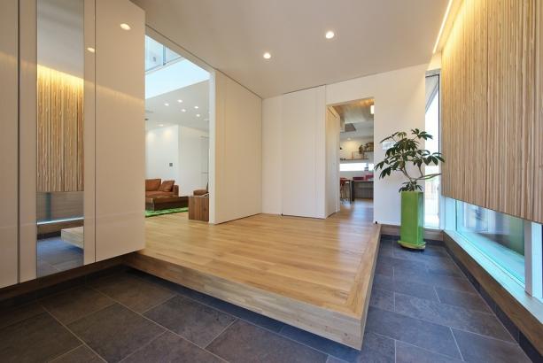 天然石のタイルが敷かれたポーチを上がると存在感のある楢無垢材の一枚板のドアと壁面。