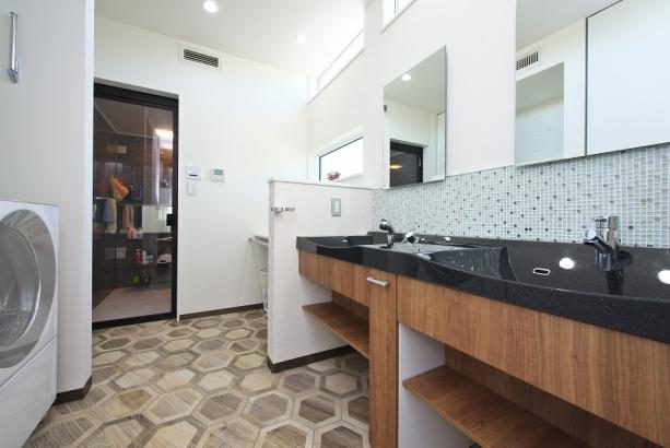 洗面台が2つ設置されたゆったりとした洗面所。床には保湿性能効果のあり亀甲模様の磁器タイル。