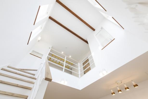 吹き抜けの天井には化粧梁を使用して空間のアクセントに。
