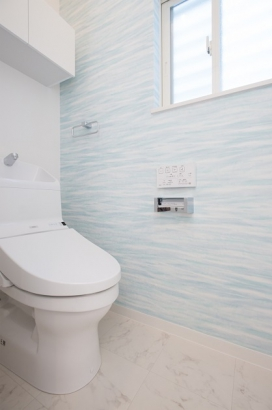 水色のアクセントサイディングを使用した、清潔感のあるトイレ。家計に嬉しい節水型です。
