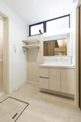 クロスや床材などがホワイト系で統一された清潔感のある洗面所。
