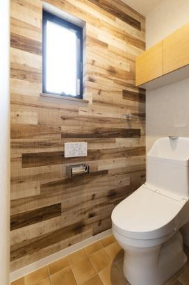 木目のアクセントクロスが目を引くトイレ。主婦に嬉しい節水型。