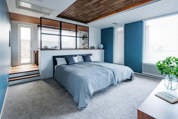 カーペット敷きのホテルライクな主寝室。ブルーグレーを基調としながらも、同系色でグラデーションさせたインテリア。大人シックに仕上げた空間でよく眠れそうです。