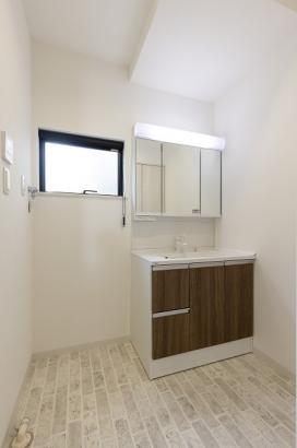 窓を設けて採光を取り入れた、明るい洗面所。壁面収納もございます。