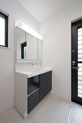 勝手口のある洗面所。洗面台の下だけでなく、三面鏡の裏にも収納が隠れています。