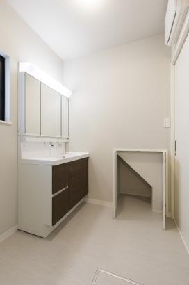 洗面所。階段下のデッドスペースを利用した壁面収納があります。