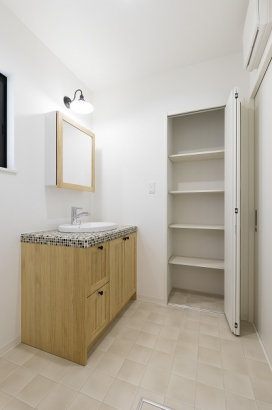 タイル調の洗面台と木の扉が可愛らしい洗面所。壁面収納があり、タオルや置き場所に困る洗剤等の備品のストックも収納出来ます。