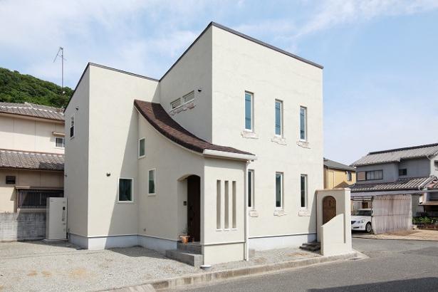玄関上部から二階へと反り上がる屋根デザインが印象深い南欧風の家