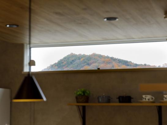 外からの視線を遮る高さの窓。山や空が見えてほっと和める。
