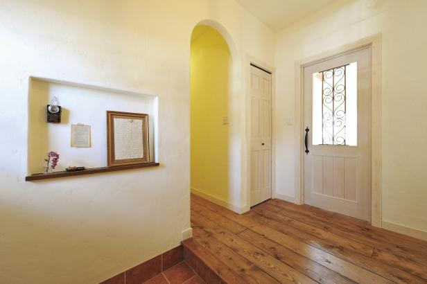 無垢材のフロア、アイアンを嵌め込んだドアがある素敵な玄関