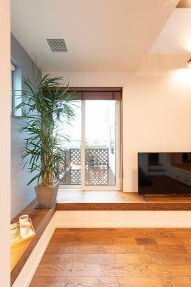 テーブルにもカウンターにもなるベンチは、外のウッドデッキとつながって部屋を広く見せる効果も