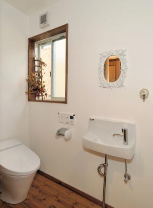 白で統一されつつ、木のぬくもりも感じられるトイレ。