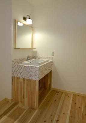 淡いピンクとオレンジのモザイクタイルを使用した洗面スペース