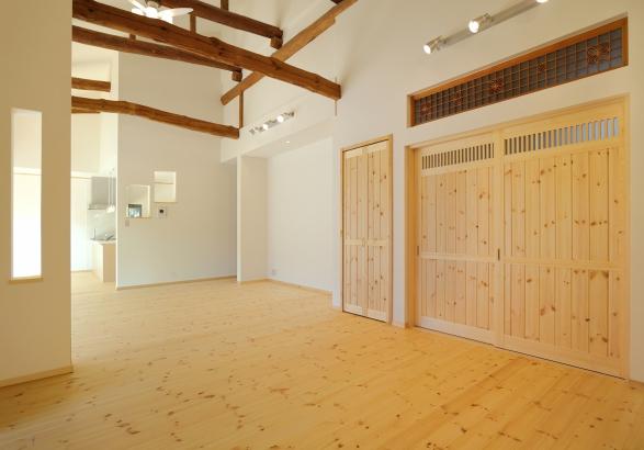 天井の立派な丸太梁はそのまま魅せ、壁は漆喰仕上げ。