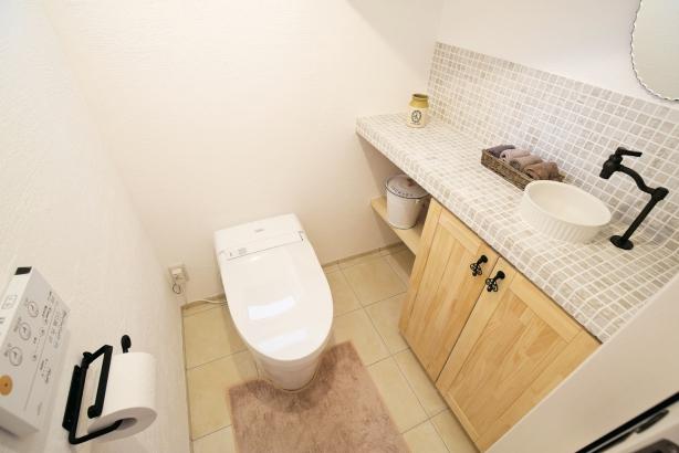 階段下の空間を有効に使ったトイレ。造作の手洗いには、お気に入りのタイルやアイテムをチョイス♪