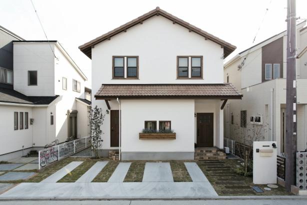 漆喰壁に瓦屋根、アンティーク調の木目の扉、レンガや枕木、花で彩られたアプローチなど、扉の向こうの住まいへの期待を抱かせます。