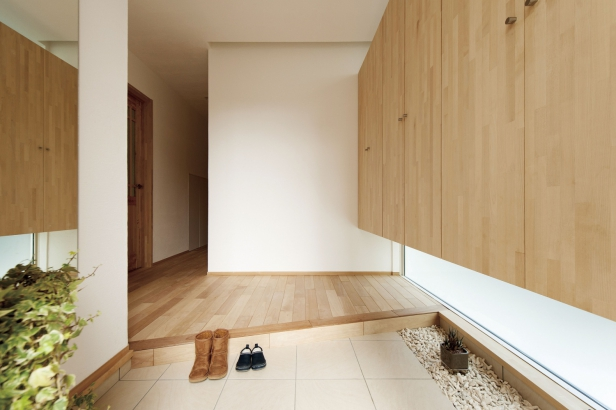 シンプルな玄関。大容量の収納で、靴や荷物が見えずスッキリ。下側に窓をつけ、足元を柔らかく照らす。