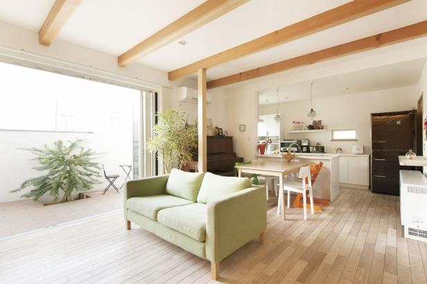 リビングの延長のようなテラスは、お子さんが元気に遊ぶこともできる。オープンなキッチンから様子を見渡せる。テラスに植えたミモザも潤いをプラス。リビングの床は明るい色合いのバーチ材、梁もナチュラルな色合いに。