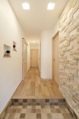 玄関の壁には個性的なサンゴ石を。ミックスカラーの土間タイルや壁のニッチも素敵。