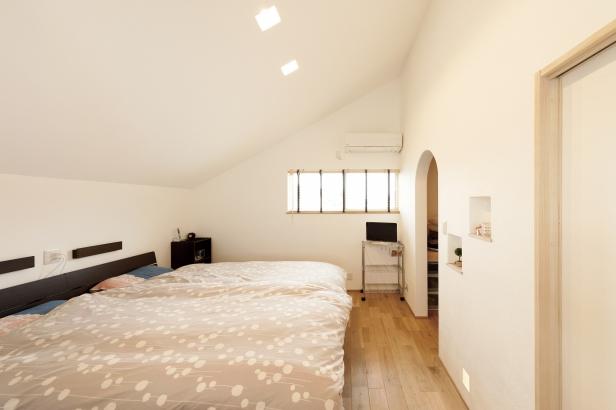 勾配天井の寝室は、ウォークインクロゼットの入口をアーチに。フットライトも設けました。
