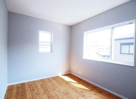 ライトグレーの塗り壁を寝室のアクセントに