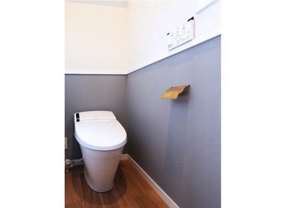 白とライトグレーのツートンカラーの塗り壁がトイレをおしゃれに演出