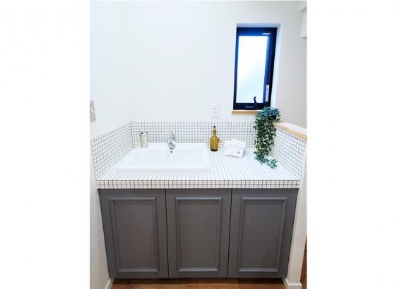 洗面台もオリジナルでおつくり。濃いグレーのキャビネットが目を引きます。