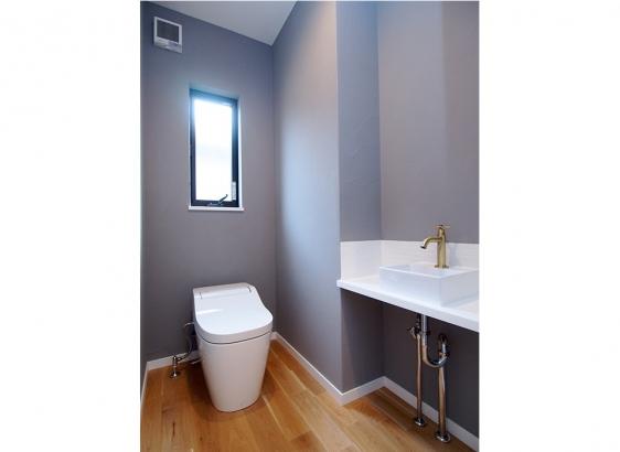 手洗い付の広々としたトイレ。グレーの塗り壁で落ち着いた印象に。