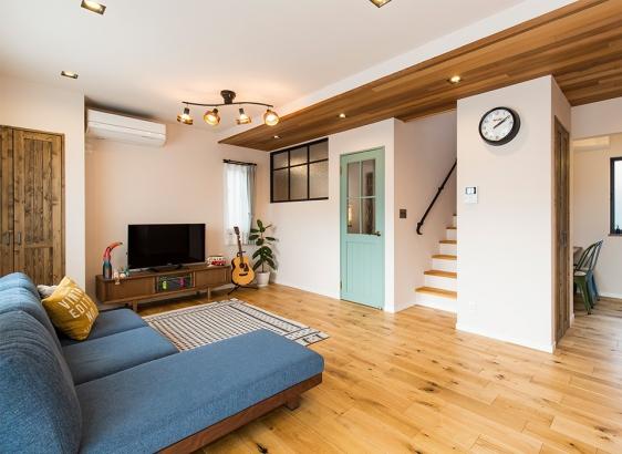 ヴィンテージライクな床に鮮やかなグリーンの扉やレッドシダ―など綺麗目アイテムを合わせて
