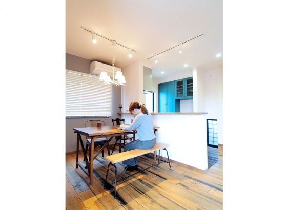 グレーの塗り壁や深いグリーンの食器棚で空間にアクセントを