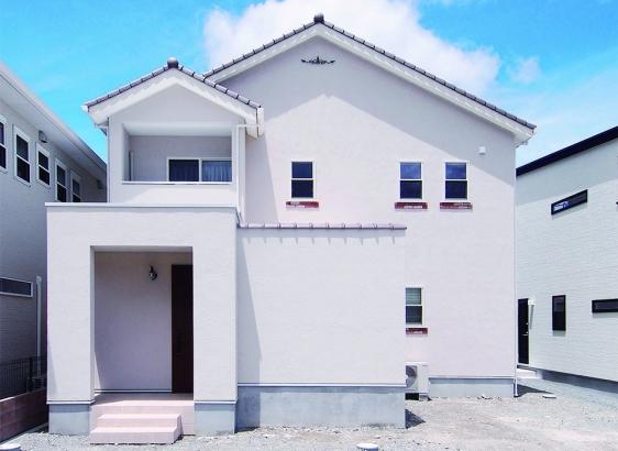 白の塗り壁に瓦の三角屋根がナチュラルかわいい外観